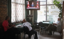 People watch a television broadcasting the speech of Turkish PM Erdogan at coffee shop in Istanbul