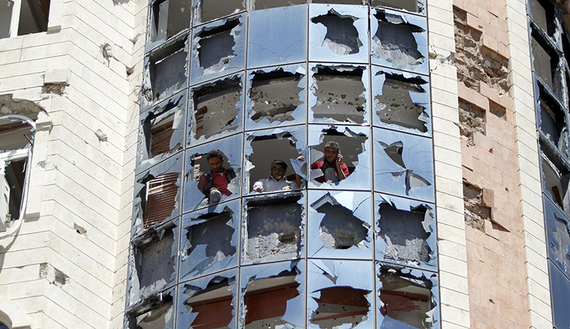 Workers clear broken glass from windows damaged by fighting between Shi'ite Houthi rebels and government forces in Sanaa